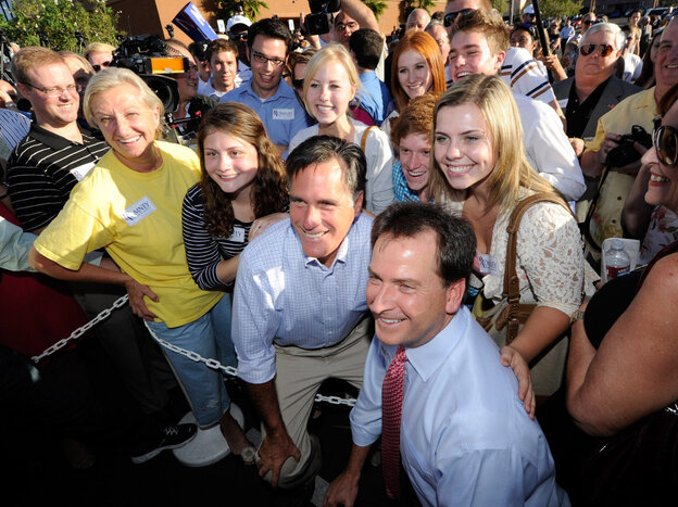 Mitt Romney and Nevada Lt. Gov. Brian Krolicki (r) take photos with supporters as Romney opens his state headquarters in Las Vegas, October 17, 2011.