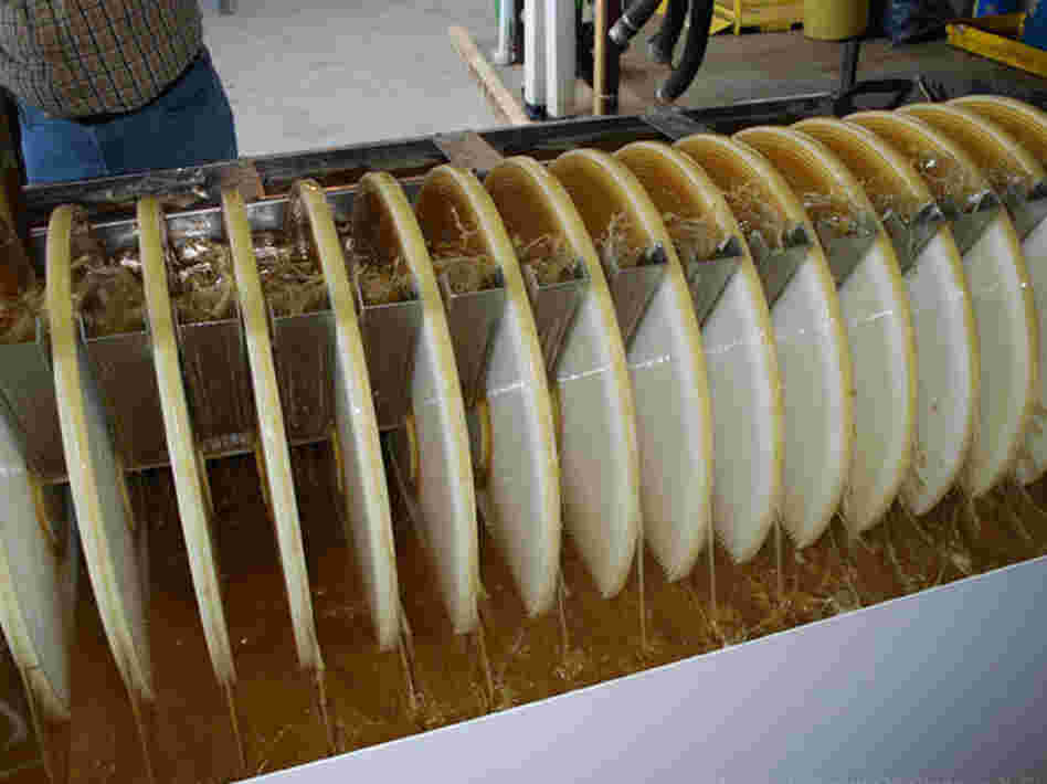 In the winning oil-removal design, spinning grooved discs pull oily water upward, where metal skimmers strain the oil away.
