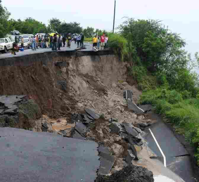 People observe the damage caused by a landslide on the Pan-American highway 55 Km south of Tegucigalpa.