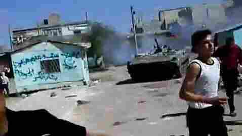 In a frame grab from a YouTube video, Syrian protesters clash with an armored military in the southern Syrian town of Dera'a last Friday, according to people in the video.