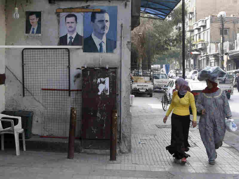 Syrian women stroll past posters of President Bashar Assad in Damascus on Monday. Assad has relied heavily on his security forces as he battles an uprising now in its eighth month.