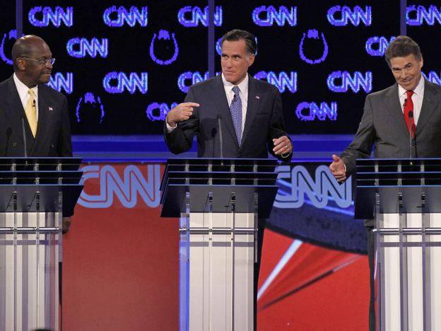 <p>Herman Cain (left) watched as former Massachusetts Gov. Mitt Romney (center) and Texas Gov. Rick Perry spoke during what became a heated Republican presidential debate Tuesday night in Las Vegas.</p>