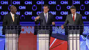Herman Cain (left) watched as former Massachusetts Gov. Mitt Romney (center) and Texas Gov. Rick Perry spoke during what became a heated Republican presidential debate Tuesday night in Las Vegas.