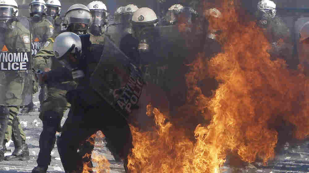 A riot policeman's clothing catches fire after being hit by a gasoline bomb during clashes with protesters Wednesday outside the Greek Parliament in Athens.