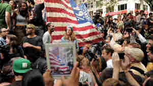 An onlooker takes a photograph of Occupy Wall Street protesters in New York's Zuccotti Park. The demonstrations were inspired by a blog post by Kalle Lasn, founder of Adbusters magazine.