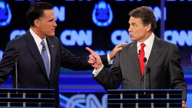 Former Massachusetts Gov. Mitt Romney (left) and Texas Gov. Rick Perry got into a heated exchange about immigration during Tuesday's GOP presidential debate in Las Vegas.
