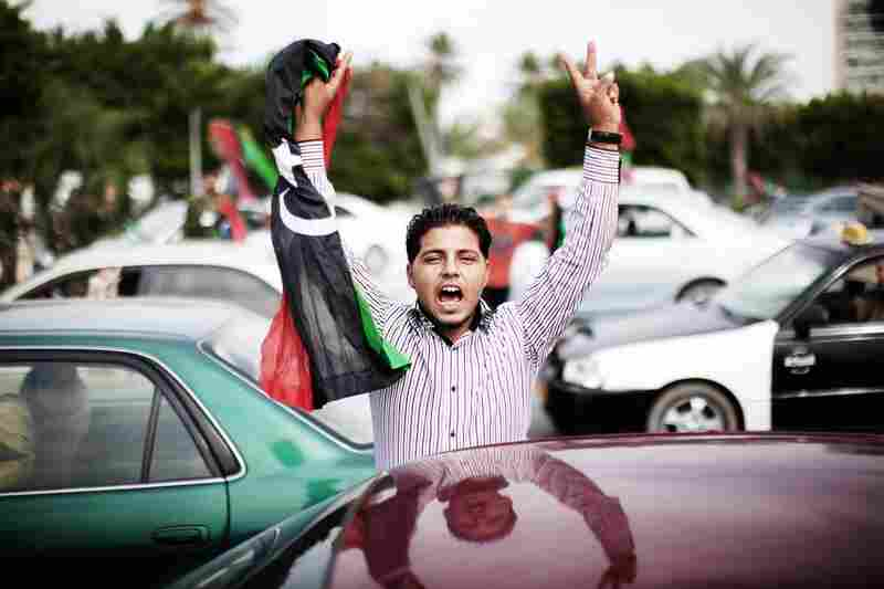 A Libyan youth holds a NTC flag during celebrations in the streets of Tripoli.