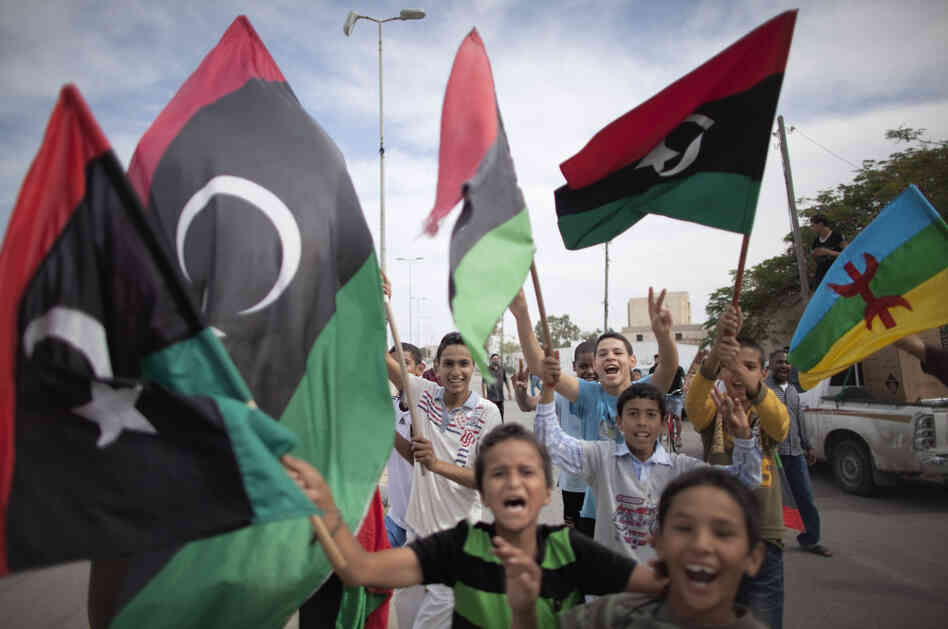 Libyan children waving National Transitional Council (NTC) flags celebrate in the streets of Tripoli following news of Moammar Gadhafi's death.
