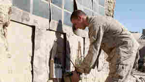 Lance Cpl. Dakota Hicks, from Laharpe, Ill., connects a radio battery to a portable solar panel system in Sangin District, Afghanistan.