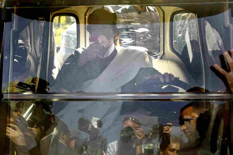 "March 2, 2011: Protected by bulletproof glass, Gadhafi leaves a Tripoli celebration of the 34th anniversary of establishing a ""republic of the masses"" in Libya. Weeks of anti-government protests have escalated into rebel forces clashing with pro-Gadhafi supporters for control of cities along the Libyan coast."