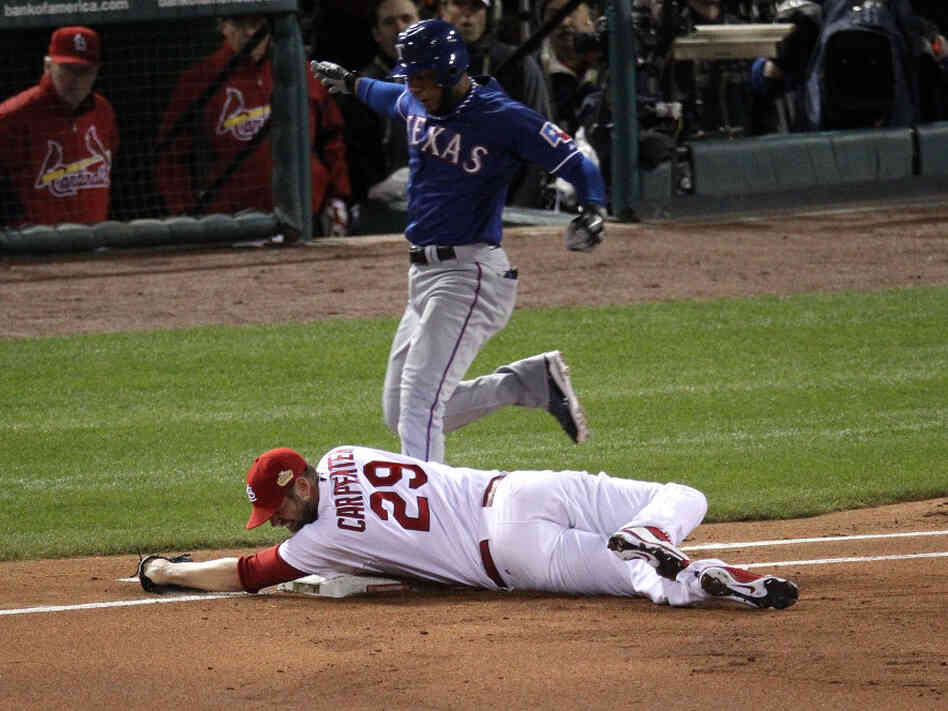 A cool out: Pitcher Chris Carpenter of the St. Louis Cardinals tags first base for an out as Elvis Andrus of the Texas Rangers reaches the base.