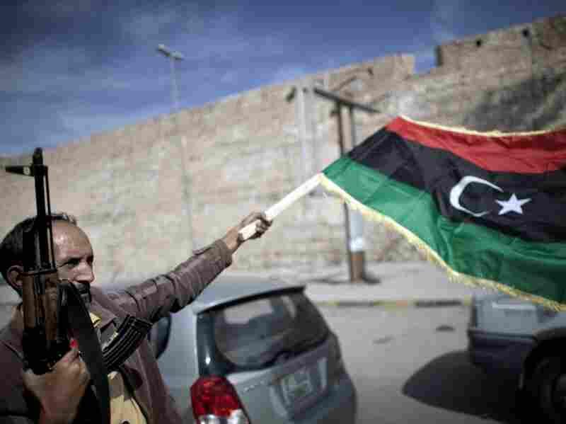 A Libyan fighter waves a Transitional National Council (TNC) flag as he celebrates in the streets of Tripoli following news of Moammar Gadhafi's capture on Oct. 20, 2011.