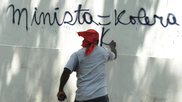 A Haitian protester in Port-au-Prince last month spray-paints a wall, equating the UN mission in Haiti (abbreviated here as MINISTA) with cholera.  (AFP/Getty Images)