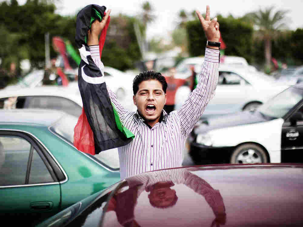 A Libyan youth holds a National Transitional Council (NTC) flag during celebrations in the streets of Tripoli following news of Moammar Gadhafi's capture on October 20, 2011.