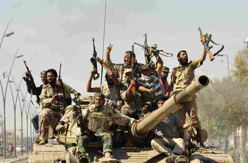 Anti-Gadhafi fighters celebrate the fall of Sirte. Libyan interim government fighters captured Moammar Gadhafi's hometown on Thursday.