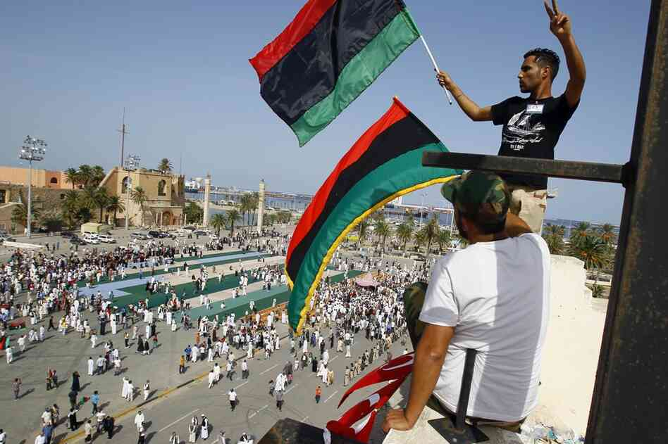 Men wave a Libyan flag after Friday prayer at Martyrs Square in Tripoli.