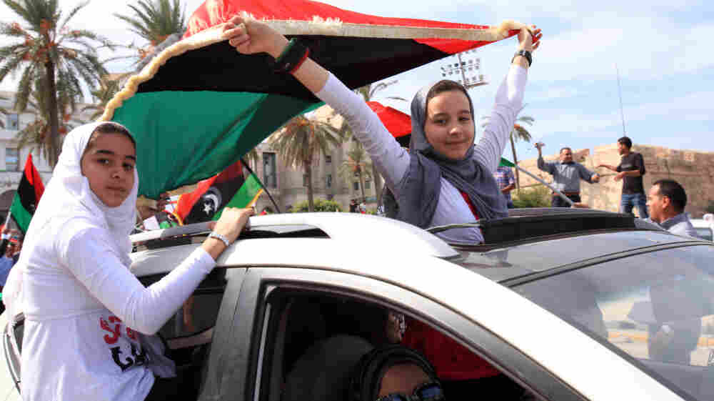 Libyan girls wave flags of the Transitional National Council as they ride through the streets of Tripoli following word of Moammar Gadhafi's death.
