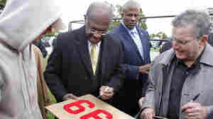 "On the day he revised his tax plan to 9-0-9, Republican presidential candidate Herman Cain signs a supporter's ""999"" sign after unveiling his ""Opportunity Zone"" economic plan in front of the Michigan Central Station, an abandoned train depot in Detroit."