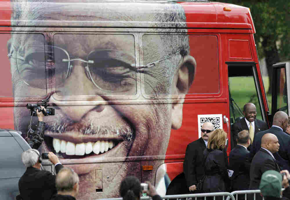 "Republican presidential candidate Herman Cain steps out of his campaign bus to at a rally where he unveiled his ""Opportunity Zone"" economic plan in front of the Michigan Central Station, an abandoned train depot in Detroit."