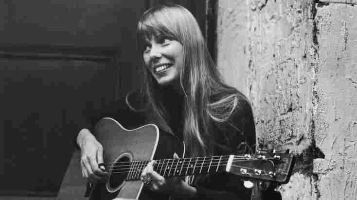 Joni Mitchell strums her guitar outside the Revolution club in London, circa 1968.