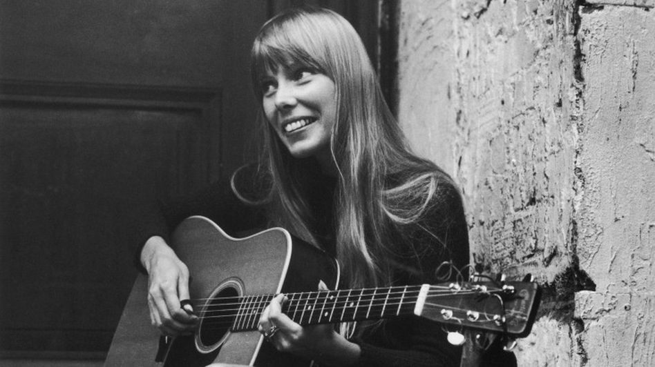 Joni Mitchell strums her guitar outside the Revolution club in London, circa 1968. (Getty Images)