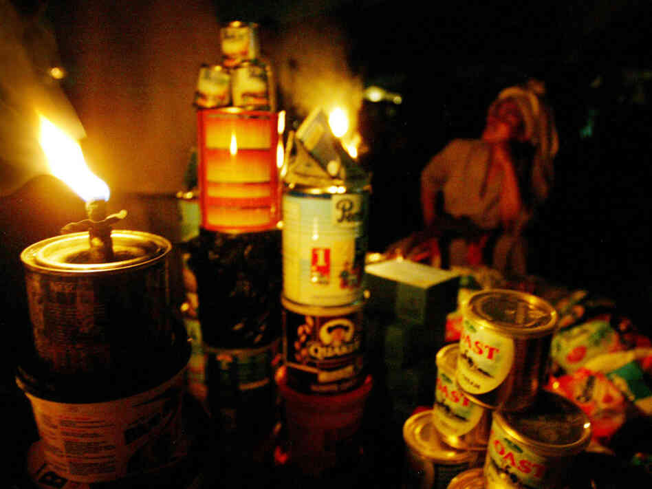 A street vendor sells her wares by the light of a kerosene wick lamp in Lagos, Nigeria. The country claims ownership of one of the world's great energy reserves, but corruption and mismanagement leave Africa's oil giant chronically short of electricity. Businesses and walled residential compounds run costly diesel generators.