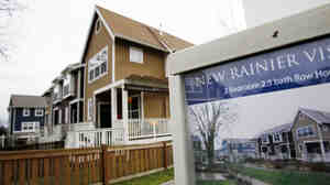 A home in Seattle is advertised for sale in January. A housing boom 140 miles north in Vancouver, British Columbia, is being fueled by buyers from India and China, while building remains at a standstill in Seattle, one housing expert says.