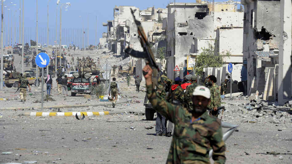 In Sirte, fighters loyal to the new government celebrate after the town's defenses finally fell, and former leader Moammar Gadhafi was killed.