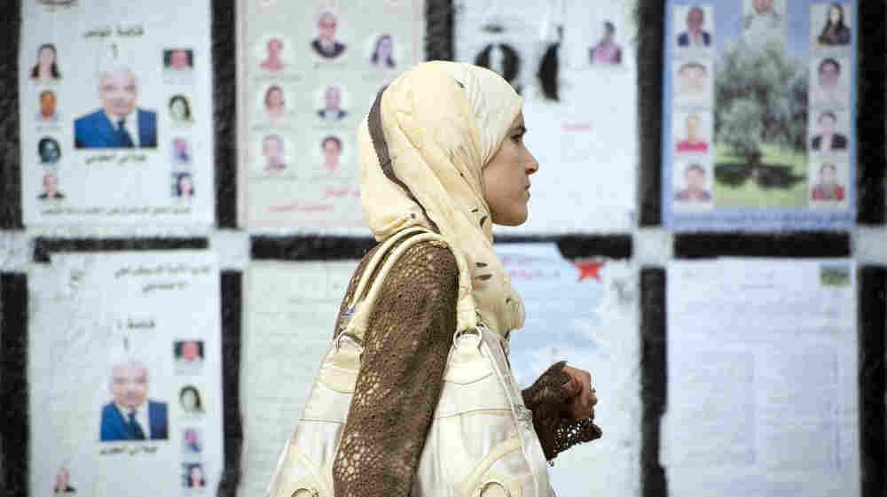 A Tunisian woman in the capital, Tunis, walks past a wall covered with posters of political candidates, on Oct. 20. Tunisia touched off the Arab uprisings this year, and it is holding elections Sunday to draw up a new constitution.
