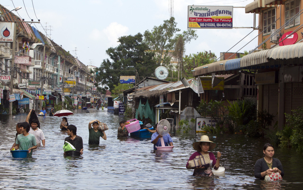 Residents make their way along flooded streets on the outskirts of Bangkok on Saturday. Thailand is experiencing the worst flooding in 50 years.
