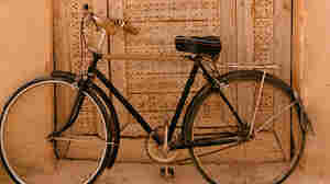 A bicycle parked against a doorway.