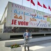 A man stands outside the international press center in Tunis on the eve of historic national election in Tunisia.