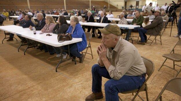 Farmer Scott Allgood, front, of Allgood, Ala., listen