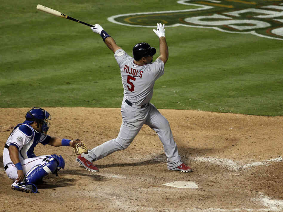 Albert Pujols of the St. Louis Cardinals hits his third home run of the game — tying a World Series single-game record — Saturday night in Arlington, Texas. His team beat the Texas Rangers 16-7 to take a 2-1 lead in the series.