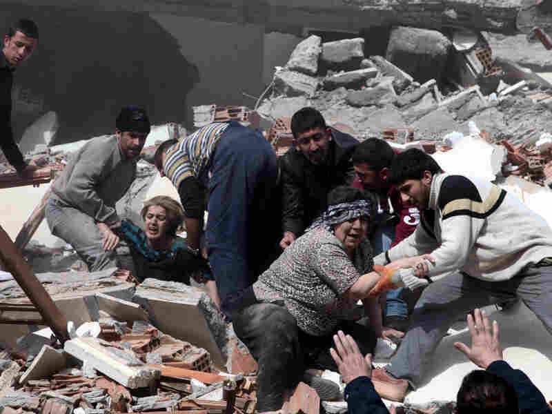 People rescue two women trapped under debris in Van eastsern Turkey after a powerful 7.2-magnitude earthquake struck eastern Turkey, collapsing about 45 buildings in Van province Sunday.