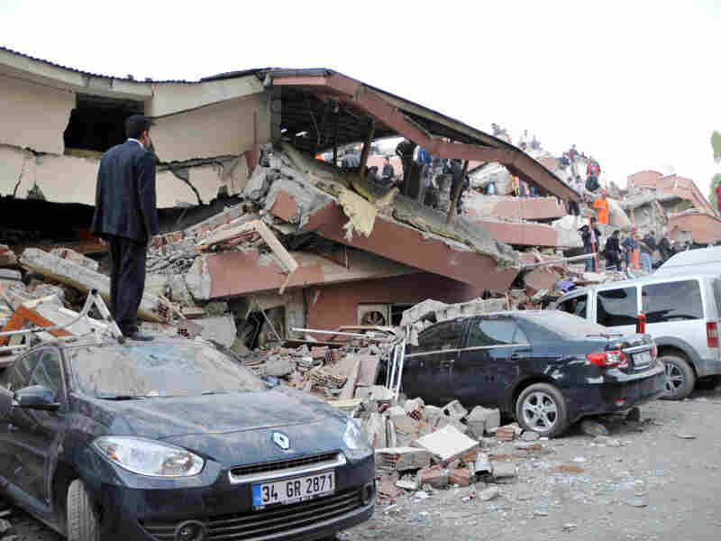 A Turkish man stands on top of a car as other Turkish men take part in a rescue operation to salvage people from a collapsed building after an earthquake in Van, in eastern Turkey on Sunday.