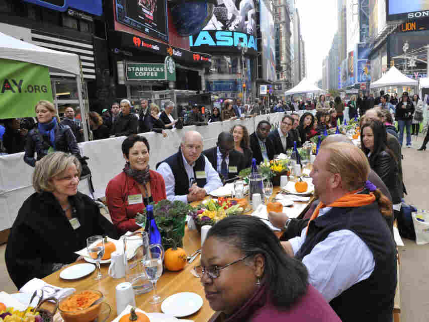 "Participants, including Mario Batali, right, at the ""Eat In,"" a Food Day lunch event in Times Square in New York on Monday."