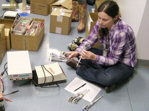 Amanda Nottke, who earned her Ph.D. from Harvard, sorts through used micropipettes that will be shipped to overseas science labs.