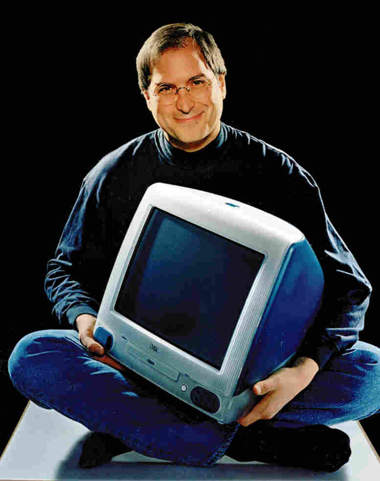 Apple CEO Steve Jobs poses with an iMac in 1998.
