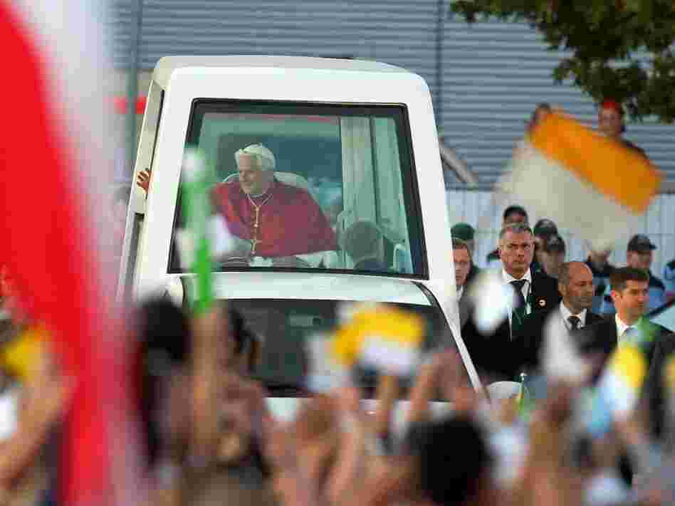 "Pope Benedict XVI rides in his popemobile through Freiburg im Breisgau, Germany, last month. The Vatican has released a document on world economics, condemning ""idolatry of the market."""