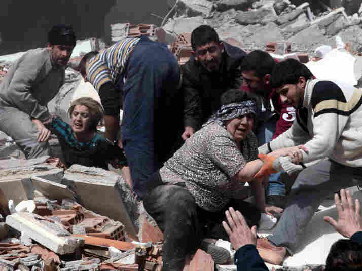 People rescue two women who were trapped under debris after a powerful 7.2-magnitude earthquake in Van, eastern Turkey, on Sunday.