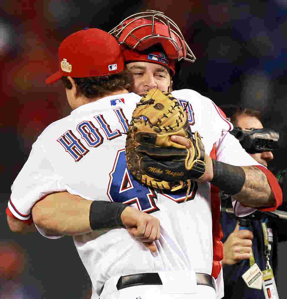 Texas Rangers pitcher Derek Holland and catcher Mike Napoli celebrate after defeating the St. Louis Cardinals 4-0 in game four of the MLB World Series.