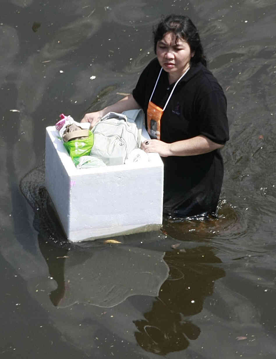 Earlier today (Oct. 24, 2011), a woman floated her belongings as she walked on a flooded road in Bangkok.