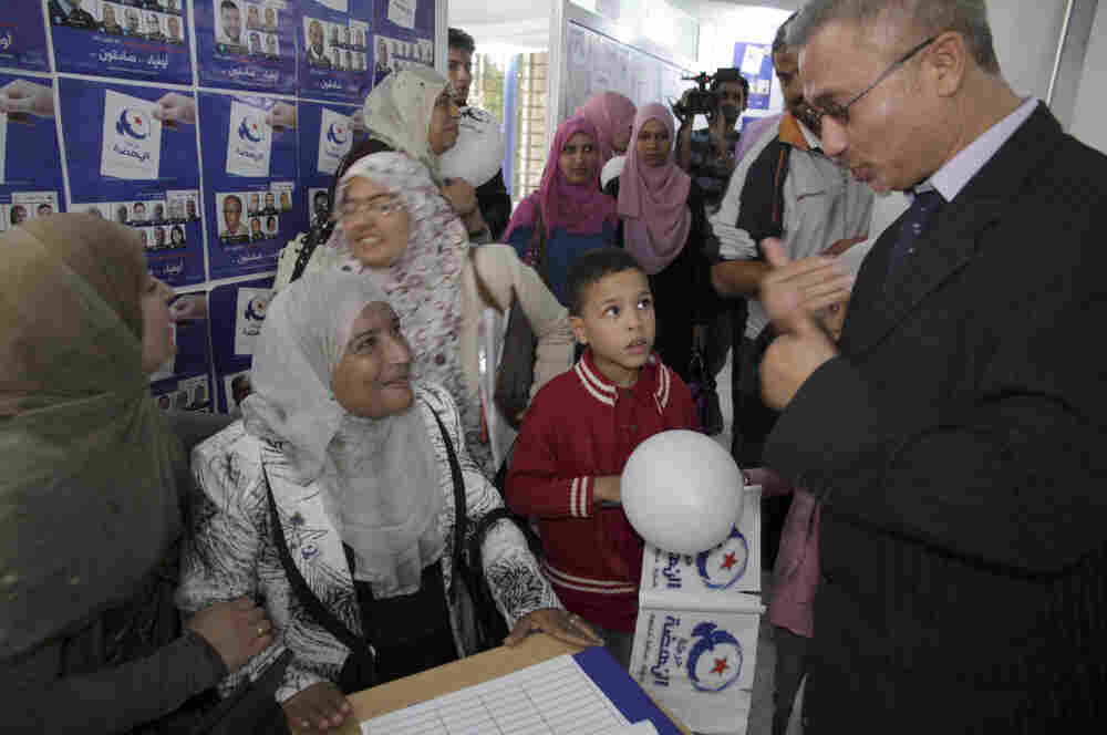 Unidentified supporters of the islamist Ennahda party reacts at the party's headquarters in Tunis on Monday.