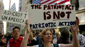Protesters hold up signs outside of Federal Hall during a demonstration against then-U.S. Attorney General John Ashcroft in 2003 in New York City.