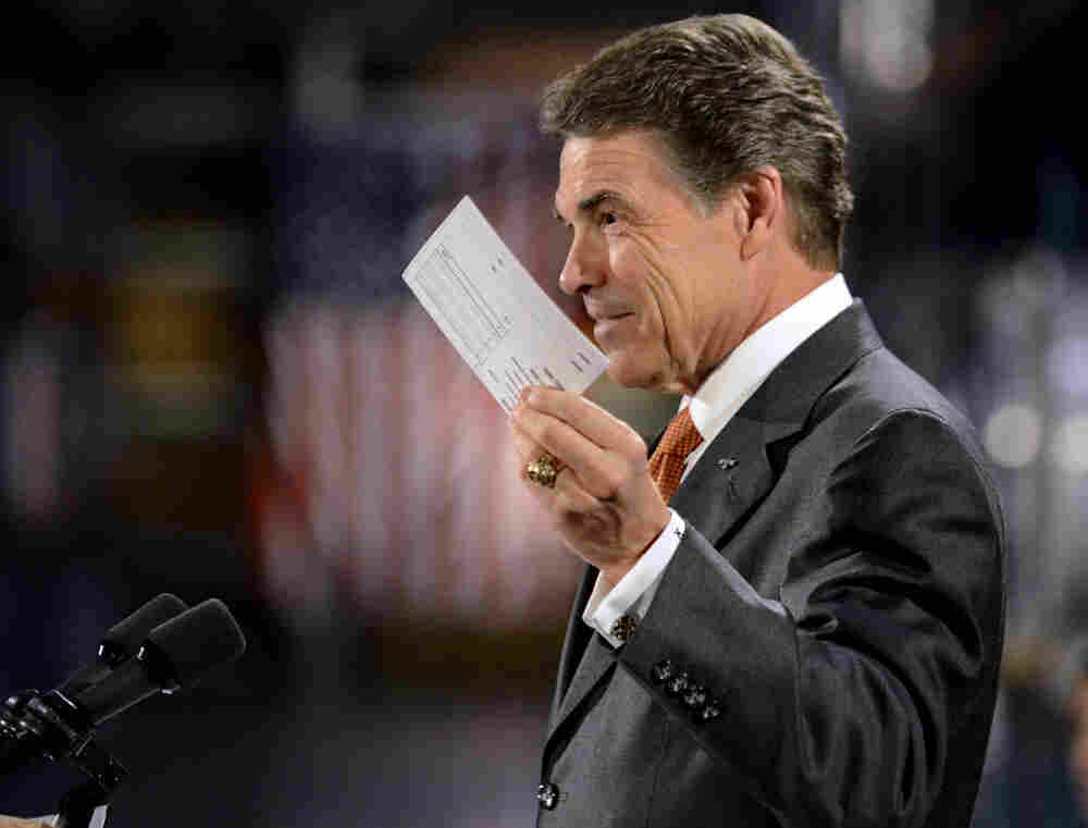 Republican presidential candidate Rick Perry holds up a postcard representing his flat tax plan Tuesday in Gray Court, S.C. Perry toured the factory and then highlighted an optional 20 percent flat tax and a deficit reduction plan.