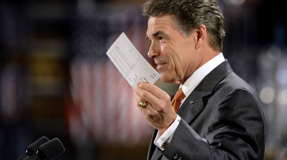 <p>Republican presidential candidate Rick Perry holds up a postcard representing his flat tax plan Tuesday in Gray Court, S.C. Perry toured the factory and then highlighted an optional 20 percent flat tax and a deficit reduction plan. </p>