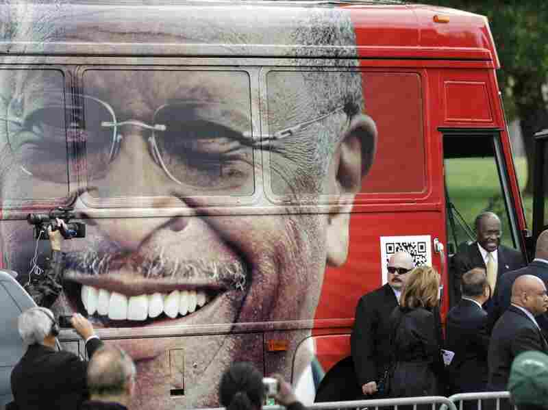 Republican presidential candidate Herman Cain steps out of his campaign bus to a rally where he unveiled his 'Opportunity Zone' economic plan in front of the Michigan Central Station, an abandoned train depot, Oct. 21, 2011 in Detroit, Michigan.