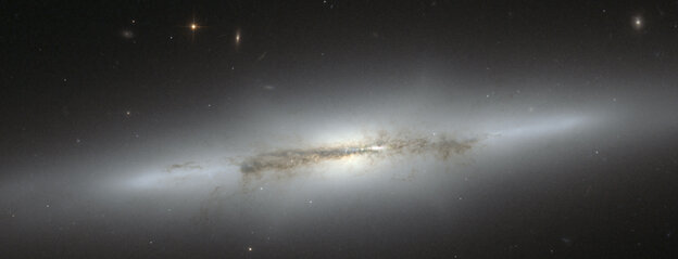 The magnificent galaxy NGC 4710 is tilted nearly edge-on to our view from Earth. This perspective allows astronomers to easily distinguish the central bulge of stars from its pancake-flat disk of stars, dust, and gas.