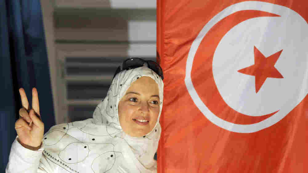A supporter of Tunisia's Islamist Ennahda party celebrates on Tuesday at the party's headquarters in Tunis. Ennahda is leading the results of Tunisia's first free and democratic election, though is not expected to win an outright majority.